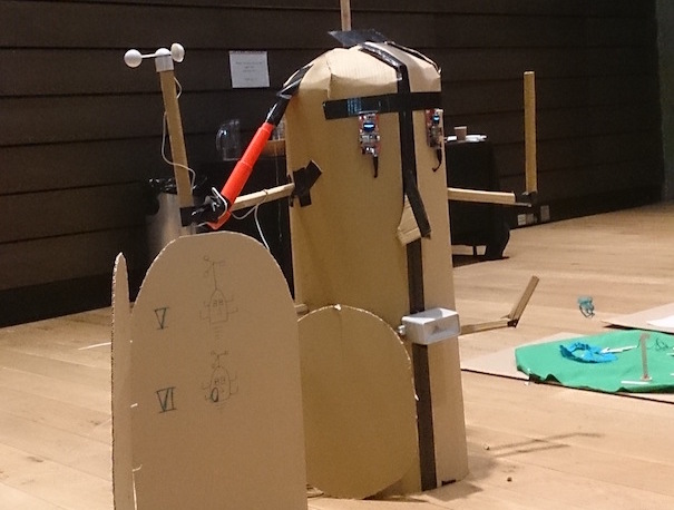 Future Machine prototype - a large cardboard head with sensors for eyes and a rainfall sensor for a mouth with 4 arms sticking up in the air and a round door.