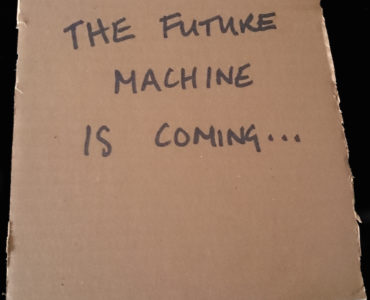 Future Machine is coming... written in black marker on cardboard square