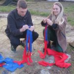 Two participants in workshops plaiting red and blue felt strips
