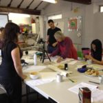 3 workshop participants working around a table with Rachel and Esther Eidinow helping them