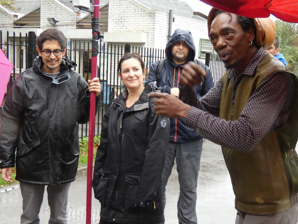 Alex Dayp talking with Rachel Jacobs, Sebastian Gaete holding the weather station pole and Dominic Price - in the rain in Finsbury Park