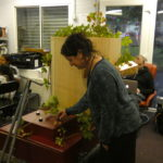 Rachel turning a dial on the Future Machine, decorated with hops in Furtherfield commons with people sitting behind