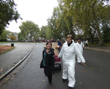 Rachel Jacobs and Ruth Catlow pulling the Future Machine uphill with the procession of people behind and Autumnal trees in Finsbury Park