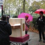 people with umbrellas around the Future Machine in the rain in Finsbury Park