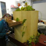 woman in a scarf talking into the copper trumpet hops decorating the machine