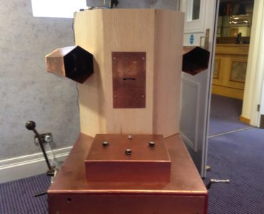 Future Machine with it's copper coloured trolley, box of dials, lever, handcrank and the Octagon with a copper rectangle in the front with a slot for the printed messages to come out and two copper trumpets on either side