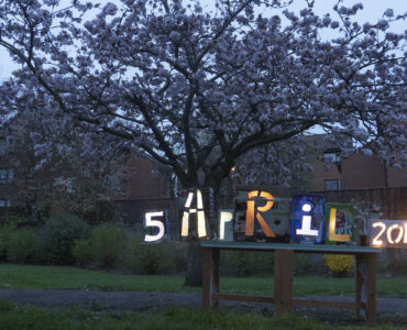 blossom tree in full blossom at dusk, light boxes on a table showing the date 5 April 2019