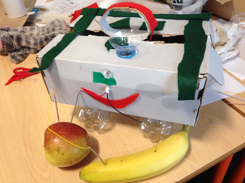 prototype machine made of recycled objects with LED light powered by and apple and a banana