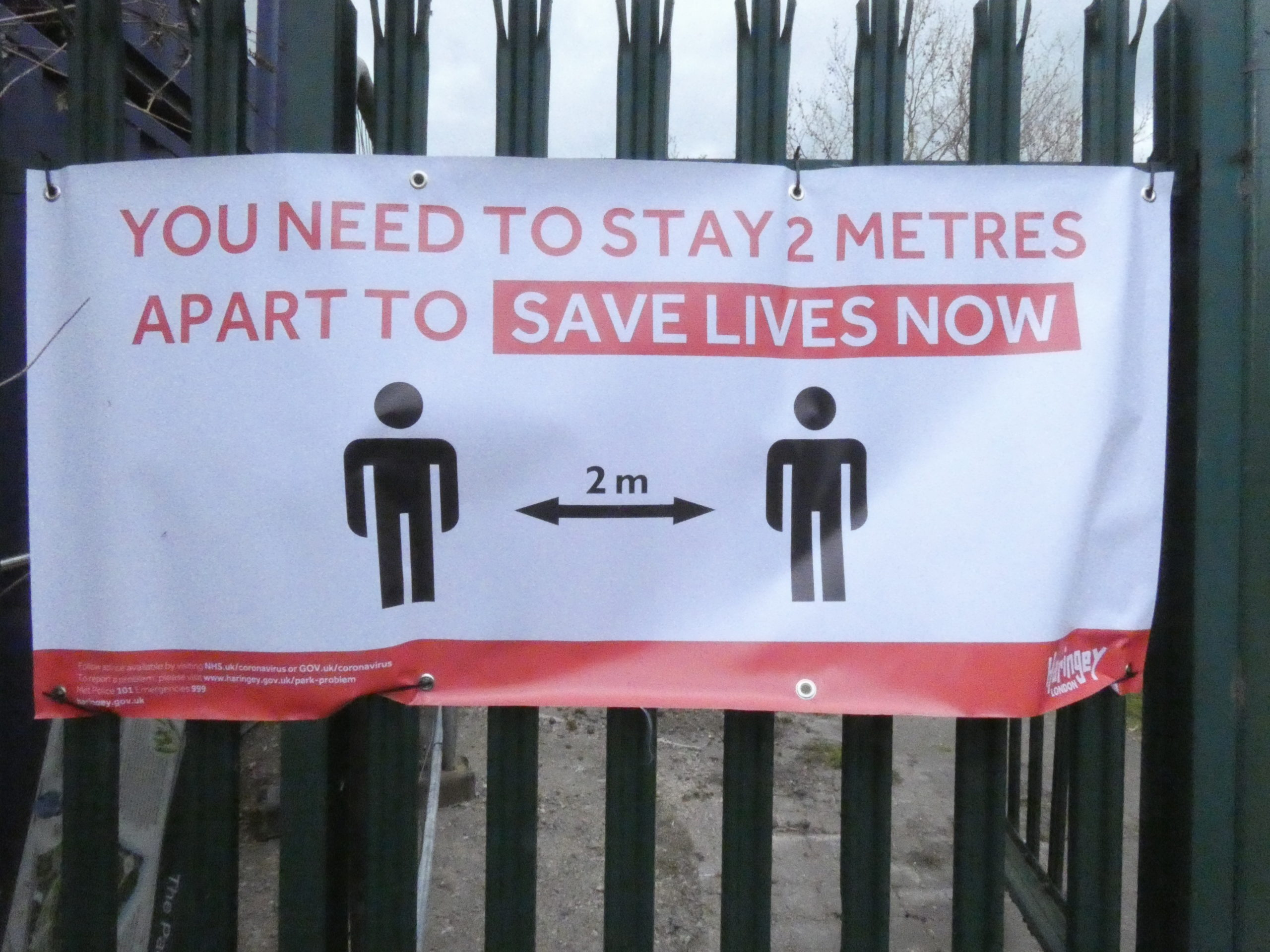 banner tied to metal fence saying You need to stay 2 metres apart to save lives now