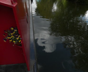 the side of our red narrowboat and the river below