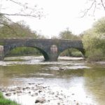 Down river on the Leven, the stone bridge and trees on the banks, the water, stones and slate