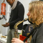 Dave playing the saxophone with Miles behind playing a Mbira