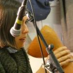 Indira singing into an upside down drum