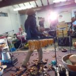 Alex throwing Autumn leaves on the floor of Furtherfield Commons, surrounded by instruments and equipment for the performance, including water drums