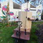back of the Future Machine in the drumming school garden with the mural behind and the lever and weather pole