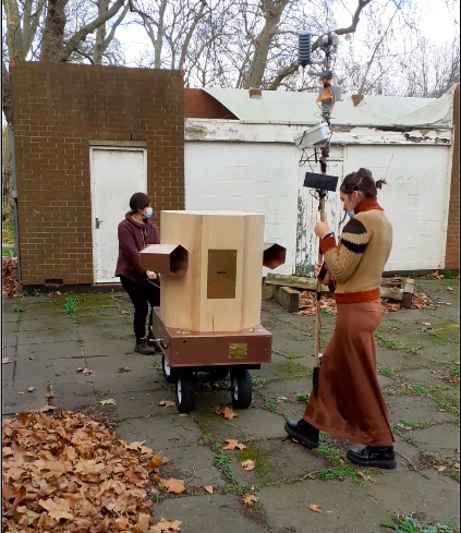 Rachel pulling the Fuutre Machine outside Furtherfield Commons with Indira in front holding the weather station on a pole