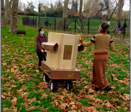 Rachel and Indira pushing the Future Machine up the hill in Finsbury Park amongst Autumn leaves