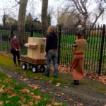 Rachel Jacobs and Dave Kemp pulling the Future Machine up hill in Finsbury Park, Indira Lemouchi is holding the weather station and walking behind
