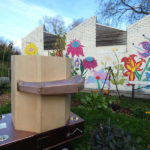 side of the Future Machine in the drumming school garden with the mural behind and the lever and weather pole, the drumming school garden and mural in the background