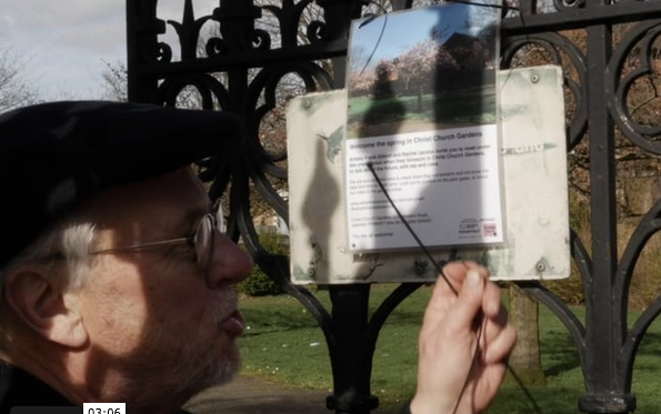 Frank putting up the poster for the When This Tree Blossom event in Christ Church Gardens on the gate, planned for Spring 2020