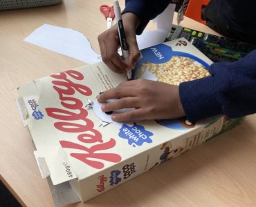 A child's hands drawing an outline of a bird onto a Kellogs Coco Pops cereal packet, with scissors in the background