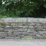 a road, a dry stone wall with engraved writing into the top of the wall (unreadable), trees