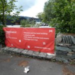 a dry stone wall and a wign for Windermere Jetty Musuem, with the museum and lake in the distance, cars in the park, trees, Claife Heights on the otherside of the lake and the sky