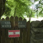 a gate and dry stpne wall with trees behind, a broken slate sign with Stock Ghyll Water Meadow (with some letters missing) and a private property sign below