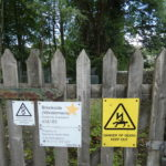 a wooden fence with signs on it, Brookside (WIndermere) Electricity Substation, Danger of Death Keep Out