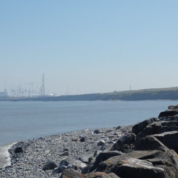 Caroline walking along the coastal path at Kilve with the sea on the left and Hickley Point C nuclear power station in the distance